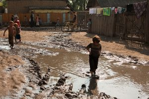 Without paved roads or even gravel, rain water turns even a simple walk through the village a journey