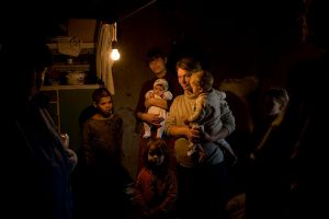 A single light bulb illuminates the home of a Roma family