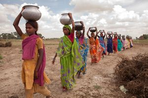Wells 01 Women walk several kilometers to gather water each day from a local stream