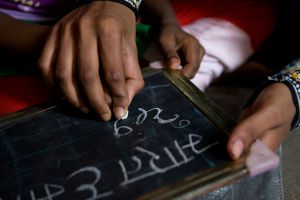 Literacy 03 Teaching hands assist learning fingers. Chalk and slate are vital to learning the alphabet throughout India